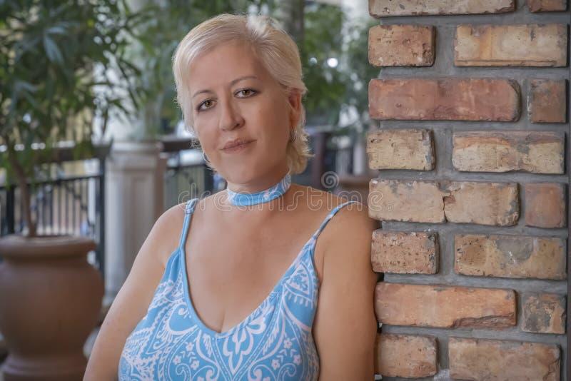 Eine reife blonde Frau lehnt sich auf einer Backsteinmauer, die Kamera mit einem Lächeln betrachtet stockfotografie