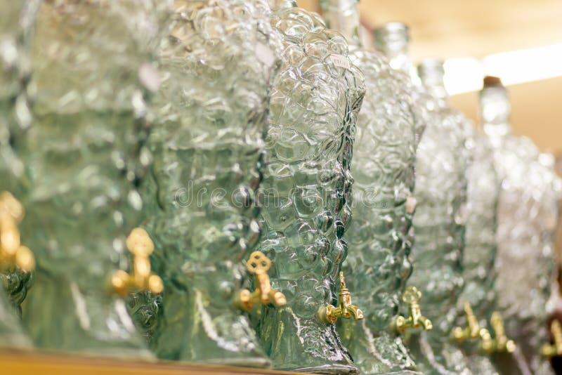 Eine Reihe dargestellte Glasflaschen mit Hähnen stehen auf dem Ladenregal stockbilder