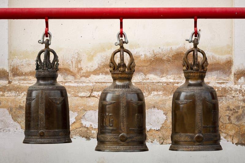 Eine Reihe der großen Glocke des Buddhismus drei im thailändischen Tempel lizenzfreie stockbilder
