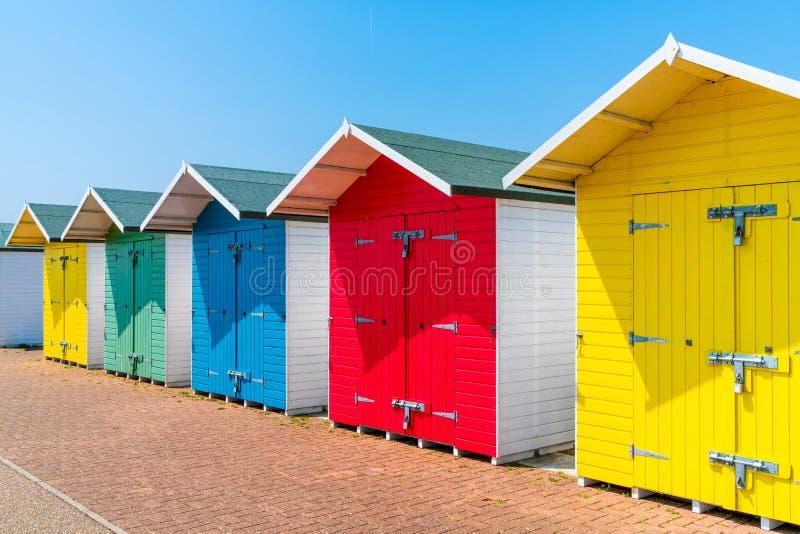 Eine Reihe von bunten hölzernen Strandhütten auf dem Strand in Eastbourne lizenzfreie stockfotos