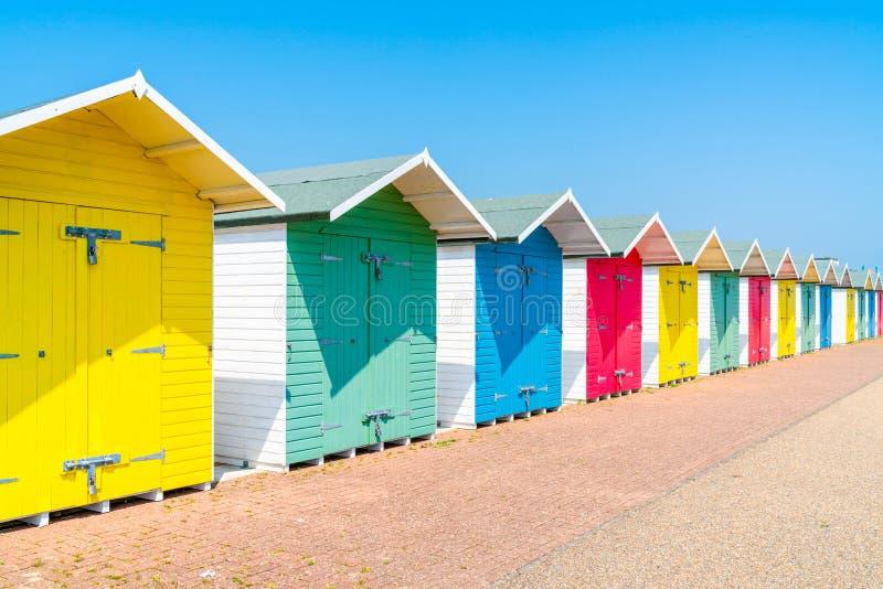 Eine Reihe von bunten hölzernen Strandhütten auf dem Strand in Eastbourne lizenzfreie stockfotografie