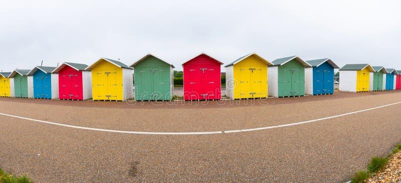 Eine Reihe von bunten hölzernen Strandhütten auf dem Strand in Eastbourne stockfotografie
