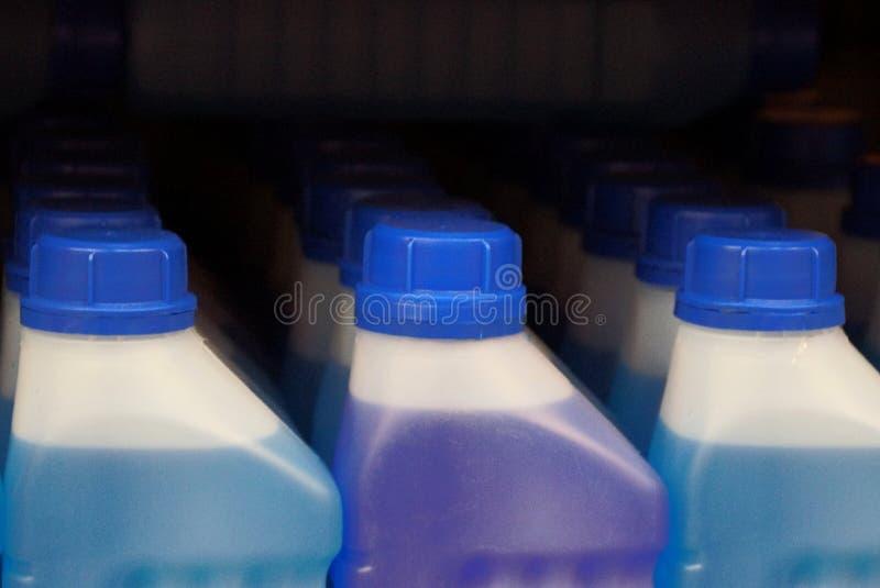 Eine Reihe von geschlossenen weißen Plastikflaschen Flüssigkeit auf dem Supermarktregal stockfotos