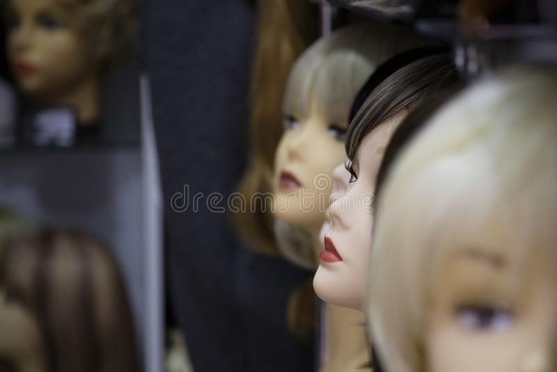 Eine Reihe von Mannequinfrauen auf einem Regal in einem Perückengeschäft stockbild