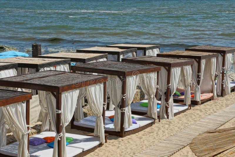 Eine Reihe von offenen Pavillons des Brauns mit weißen Vorhängen auf dem Strandsand nahe dem Meer lizenzfreies stockfoto