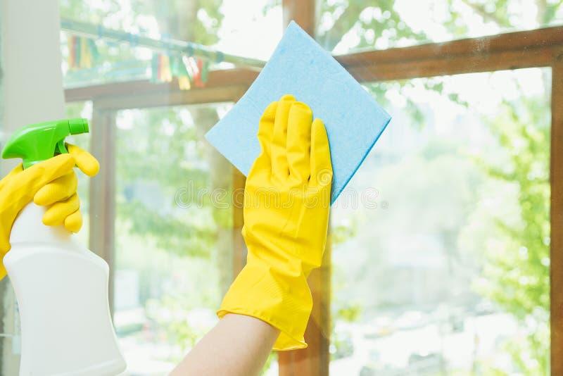 Eine Reinigungsfirma säubert das Fenster des Schmutzes Hausfrau poliert die Fenster des Hauses stockbild