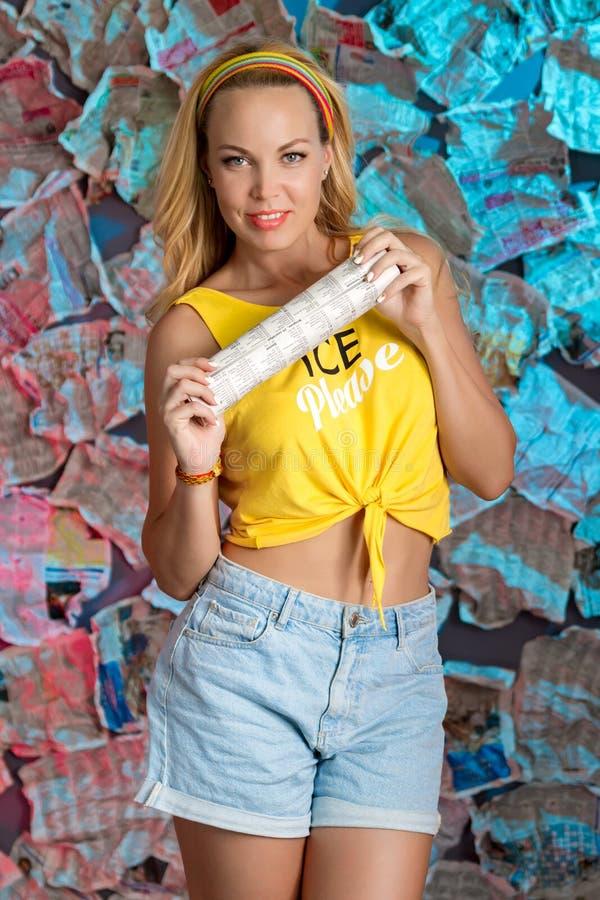 Eine reizend junge Frau in einer gelben Bluse mit einer Zeitung stockbild
