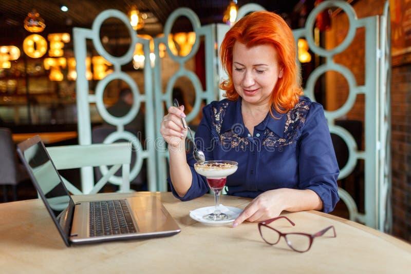 Eine reizende Frau, sitzt in einem Café mit einem Laptop und isst einen köstlichen Nachtisch stockfoto