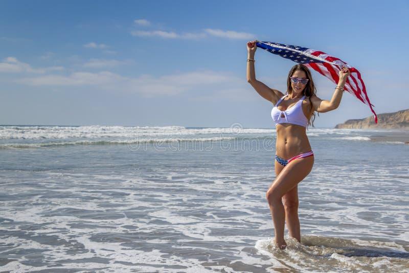 Eine reizende patriotische Brunette Modell-Poses On The-Küste mit einer amerikanischen Flagge stockbilder