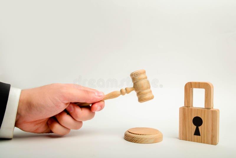 Eine Richter ` s Hand mit einem Hammer nahe einem hölzernen Verschluss Annullierung von Bankgeheimhaltung Schutz von Rechten und  stockfoto