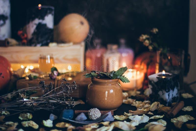 Eine Ritual-Halloween-Hexereiszene mit Kerzen, Kräuter, Weinleseflaschen auf dem rustikalen Hintergrund lizenzfreie stockfotografie
