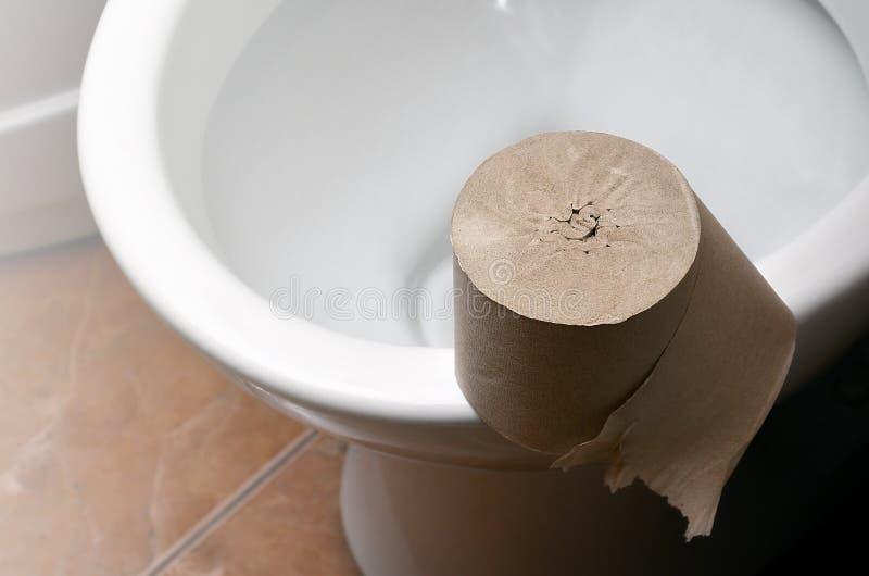 Eine Rolle des grauen Toilettenpapiers liegt auf einer weißen keramischen Toilette im bathroo stockfotos