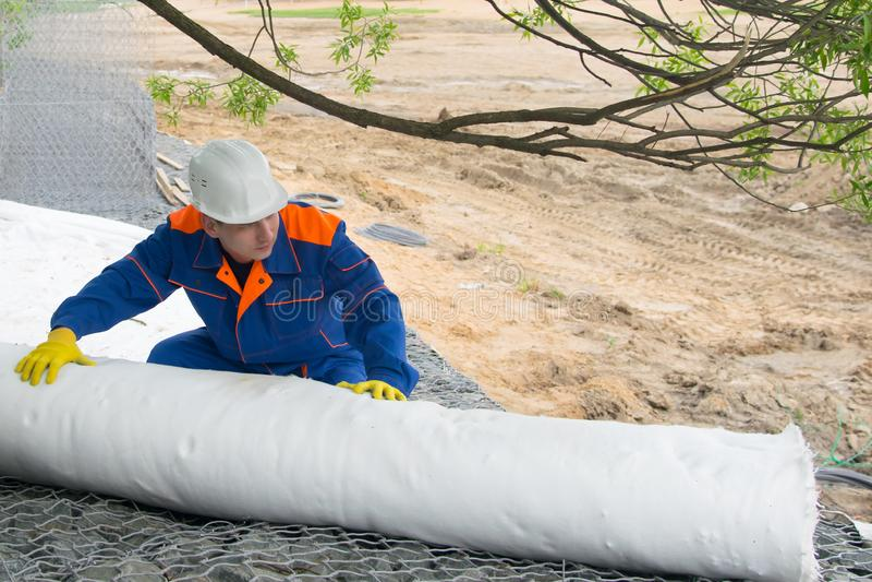 Eine Rolle des Stoffes, zum der Oberfläche des Bodens zu schützen, eine Arbeitskraft in einer blauen Uniform und einen weißen Stu stockfoto