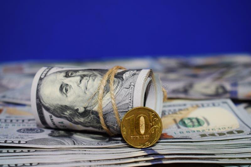 Eine Rolle von Dollar und eine Münze von 10 russischen Rubeln auf dem Hintergrund von zerstreut hundert Dollarscheinen lizenzfreies stockfoto