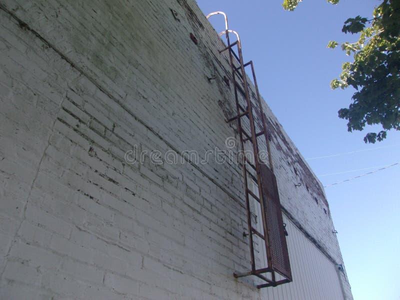 Eine rostige Leiter auf Seite von Gebäude 2 stockfotografie