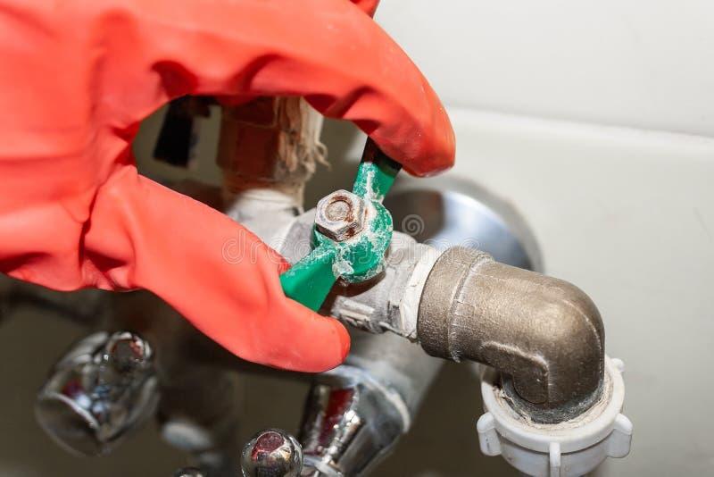 Eine rot-behandschuhte Hand dreht einen grünen Griff auf einem Verbindungsventil auf einem Chrom überzogenen Hahn, bedeckt mit Ka stockfoto