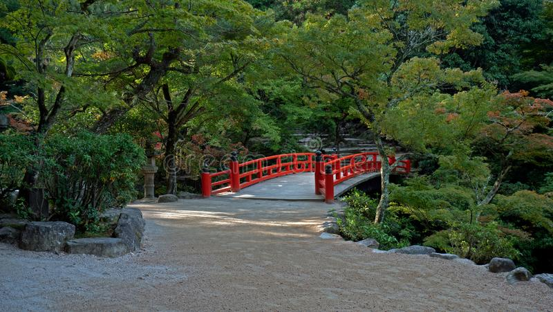 Eine rote Brücke kreuzt einen Fluss in einem klassischen japanischen Garten lizenzfreie stockbilder