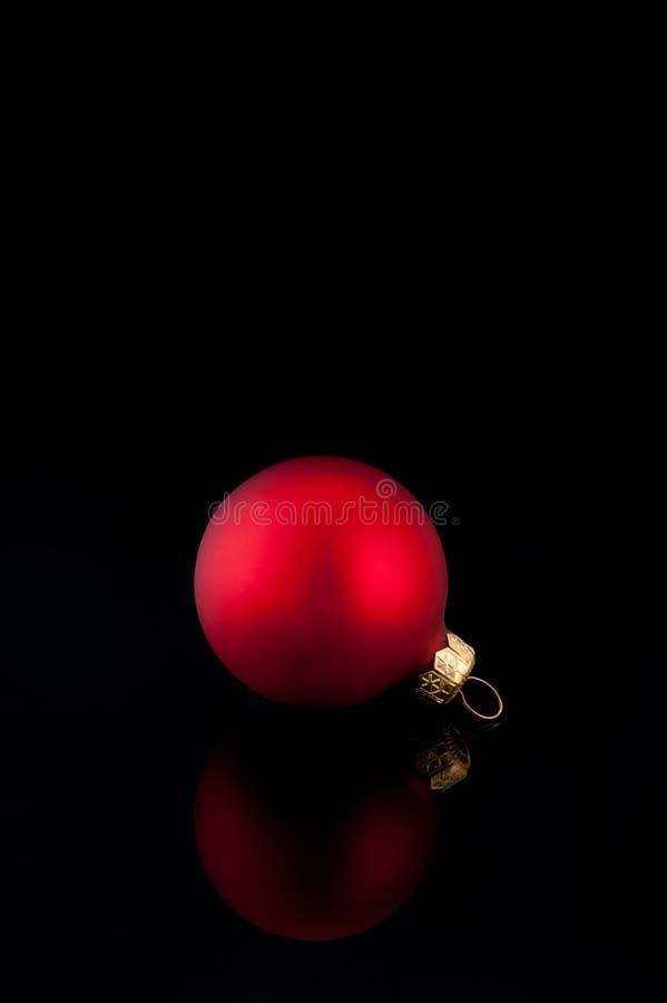 Eine rote Satin Weihnachtskugel auf schwarzem Hintergrund stockbilder