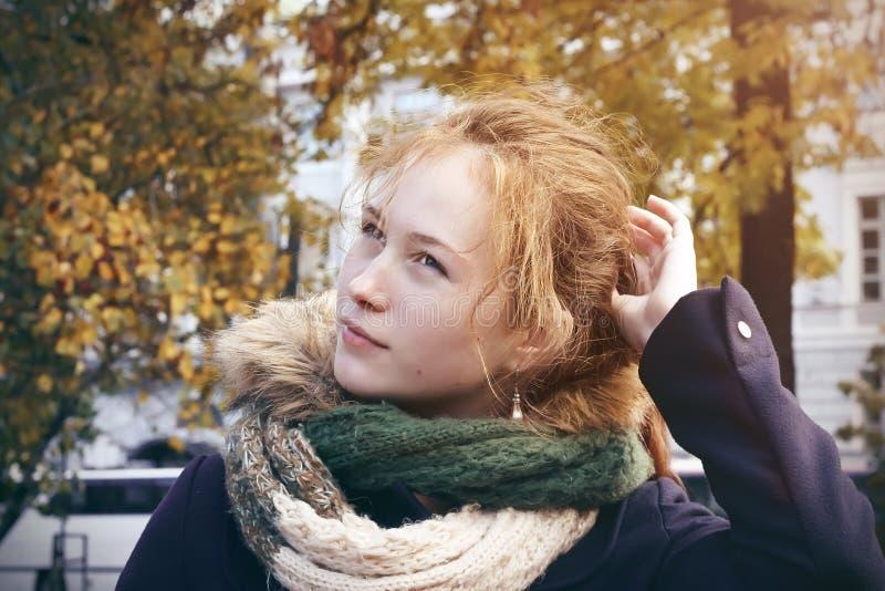 Eine rothaarige Mädchenstellung mitten in dem Stadt Park im Herbst lizenzfreie stockfotos