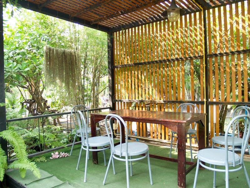 Eine ruhige Ecke, zum von den Büchern im Garten und durch grüne Bäume umgeben zu lesen lizenzfreie stockbilder