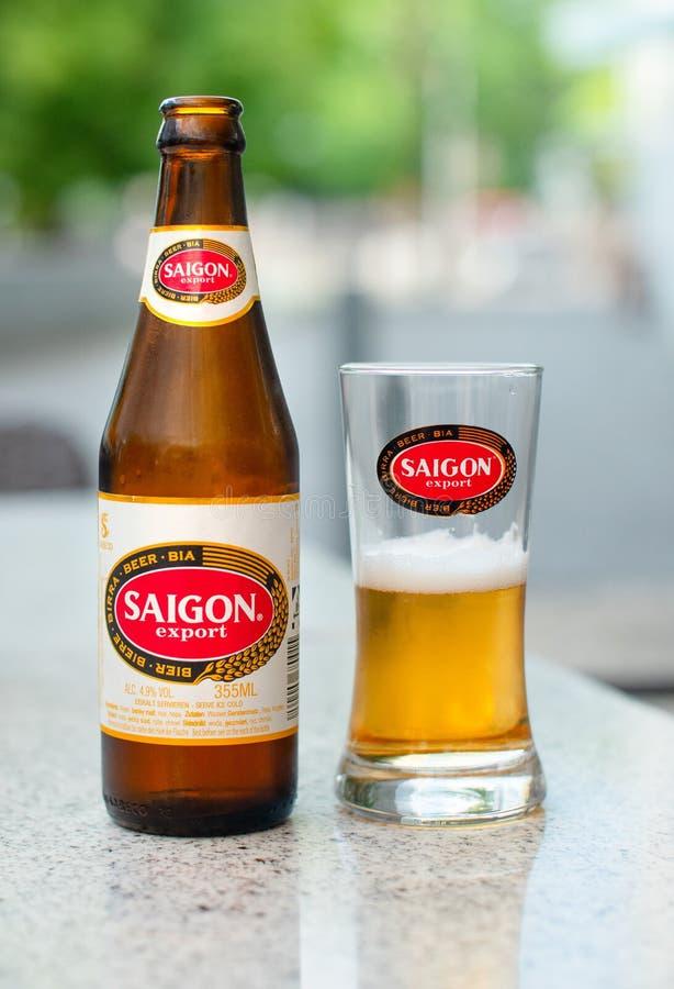 Eine Saigon-Bierflasche und ein Glas auf einer Marmortabelle an einem Straßencafé stockbilder