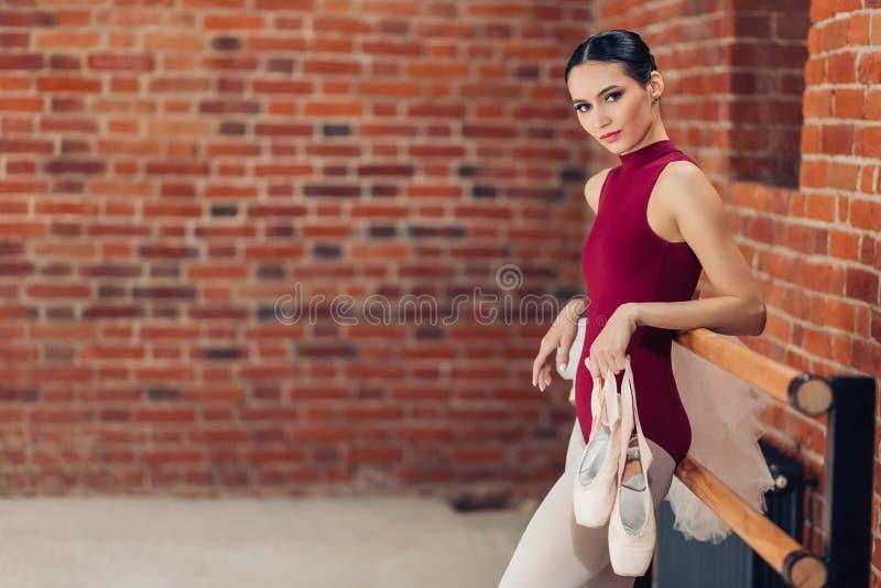 Eine schöne dünne junge Ballerina, die pointe Schuhe für das Tanzen hält stockbilder