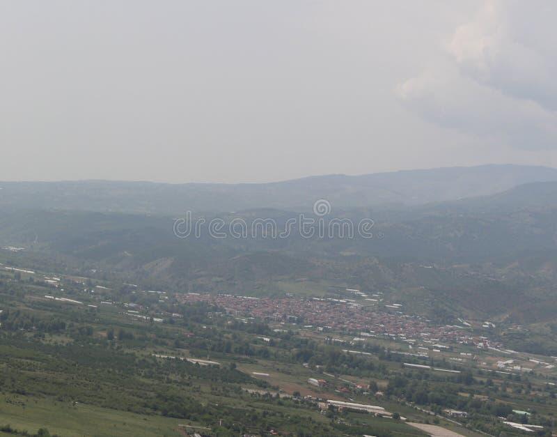 Eine schöne Ansicht des gegenüberliegenden Ograjden-Berges, des Dorfs, des Himmels und des Feldes stockfotografie