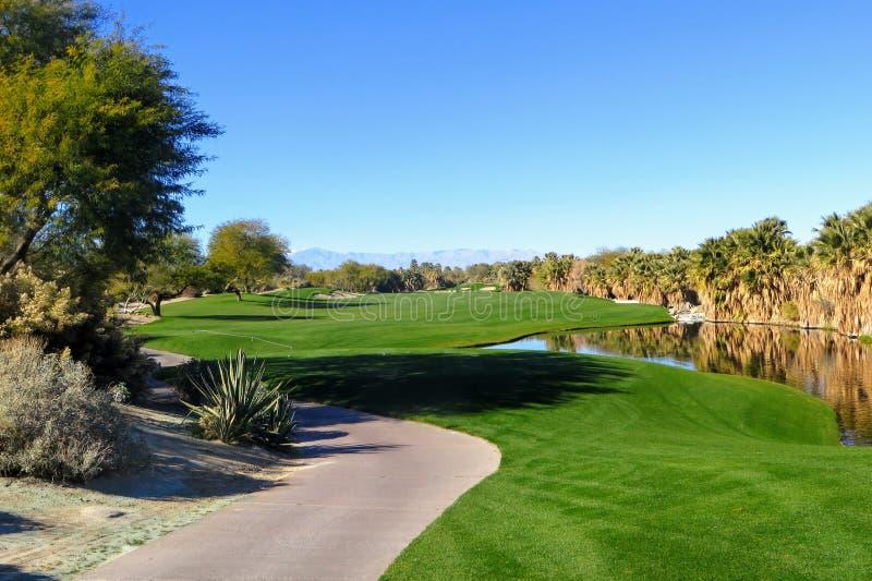 Eine schöne Ansicht einer Gleichheit 5 mit der Wüste, die das Loch sowie einen Teich umgibt Der Golfplatz ist im Palm Springs lizenzfreie stockfotografie