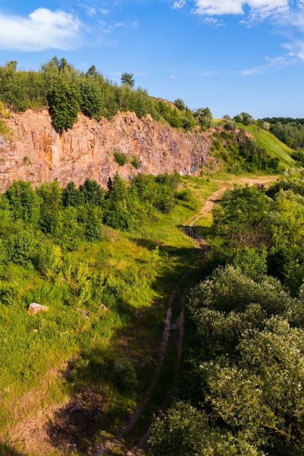 Eine schöne Ansicht von oben genanntem auf dem Schotterweg, der zwischen den Wald und einen bloßen Felshügel geht stockfoto