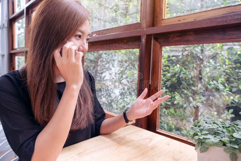 Eine schöne Asiatin, die an einem Telefon für Geschäft spricht stockbild