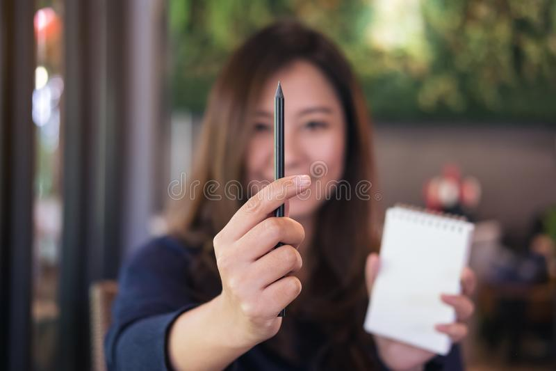 Eine schöne Asiatin, die Notizbuch und schwarzen Bleistift zum Maß im Zeichnungsprozeß im Café hält stockfoto