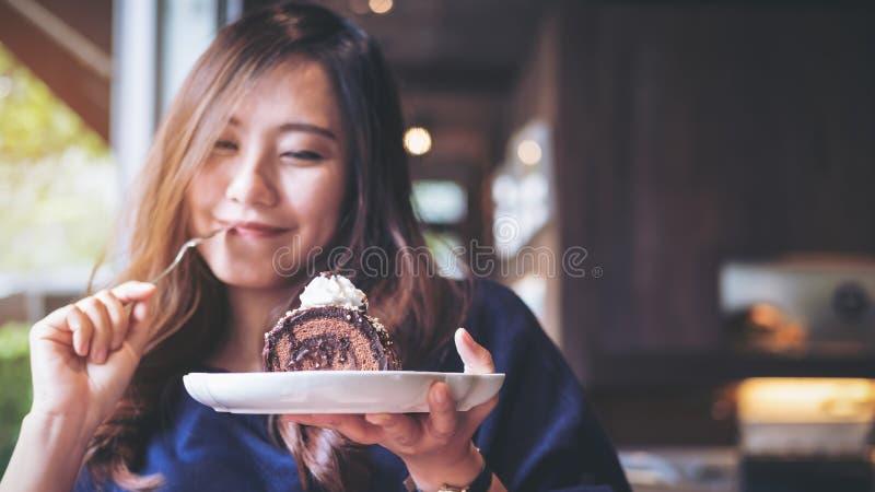 Eine schöne Asiatin, die Schokoladenkuchenrolle und -Schlagsahne halten und Gabel mit dem Fühlen glücklich und genießen, im Café  stockbild