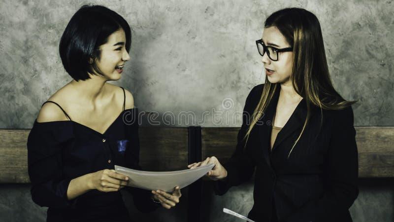 Eine schöne Asiatin sitzt auf einem Holzstuhl während für ein Interview mit dem Personal Ausschuss, Konzept der Firma von stockfoto
