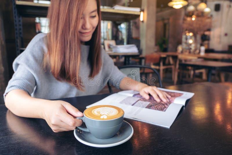 Eine schöne asiatische Frauenlesezeitschrift beim Trinken des Kaffees im modernen Café stockfotos