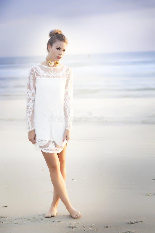 Eine schöne blonde Frau mit ihrem Haar in einem Brötchen mit einem kurzen weißen Spitzekleid, das auf dem Strand steht lizenzfreies stockfoto