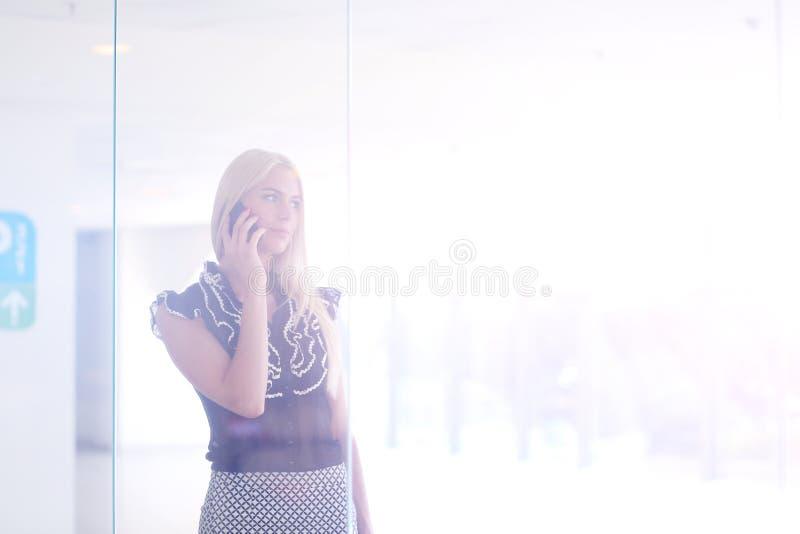 Eine schöne blonde Geschäftsfrau spricht am Telefon stockfoto