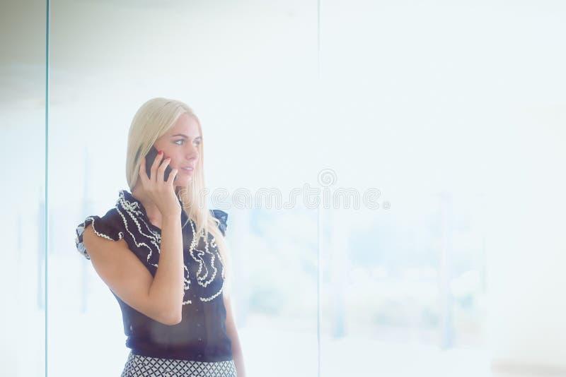 Eine schöne blonde Geschäftsfrau spricht am Telefon lizenzfreie stockfotos