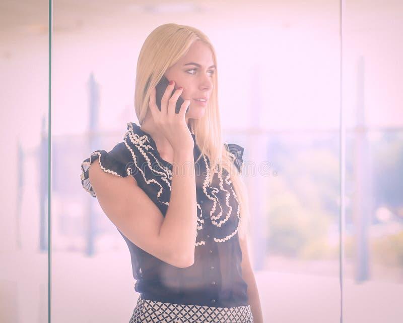Eine schöne blonde Geschäftsfrau spricht am Telefon lizenzfreies stockbild