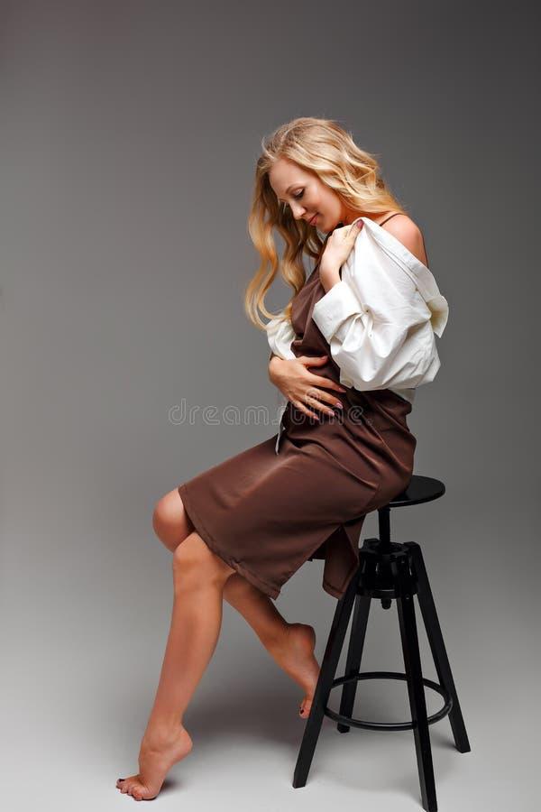 Eine schöne blonde junge schwangere Frau, die ein braunes Umstandskleid und ein weißes aufgeknöpftes Hemd trägt, sitzt auf einem  lizenzfreies stockfoto