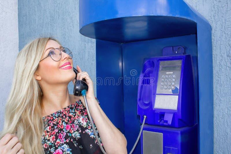 Eine schöne Blondine in den Gläsern hält einen Telefonhörer in einem Münztelefon Schön, lächelnd, den Himmel betrachtend und O sp lizenzfreie stockfotografie