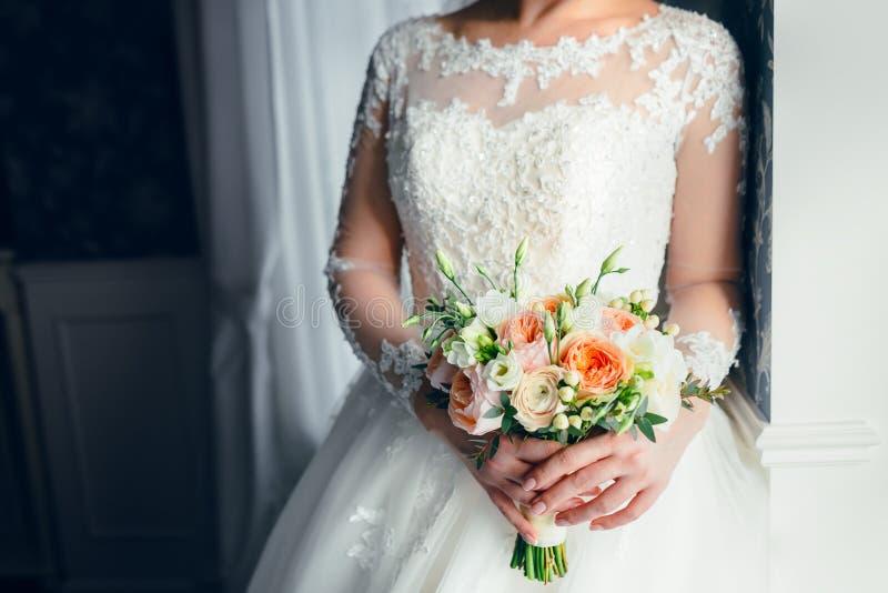 Eine schöne Braut steht nahe dem Fenster und hält einen Hochzeitsblumenstrauß mit weißen Rosen und Pfirsichpfingstrosen Nahaufnah stockfotos