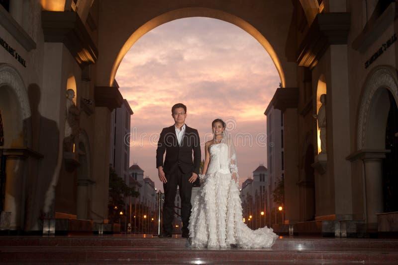Eine schöne Braut und ein hübscher Bräutigam an der christlichen Kirche während der Hochzeit. lizenzfreie stockfotos