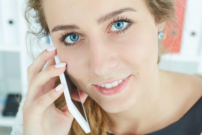 Eine schöne erfolgreiche junge Frau, die am Telefon im modernen Büro spricht lizenzfreies stockfoto