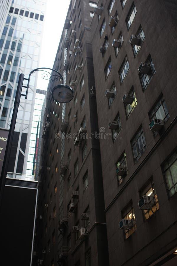 Eine schöne Gasse zwischen hohen Gebäuden mit einem Straßenkämpfer auf der Insel von Hong Kong stockfotografie