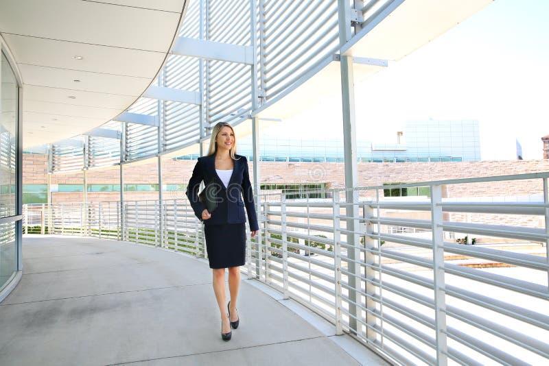 Eine schöne Geschäftsfrau, die in ein Geschäftsgebäude geht lizenzfreie stockfotos