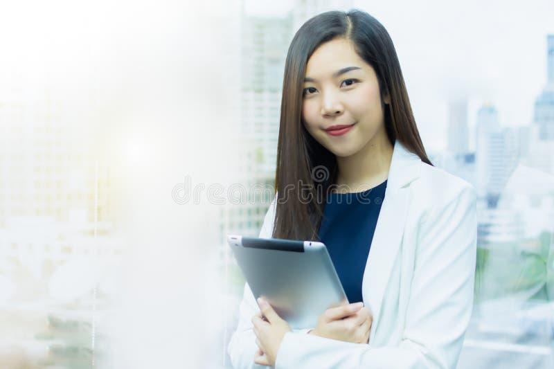 Eine schöne Geschäftsfrau mit weißer Klage unter Verwendung der Tablette für das Arbeiten lizenzfreie stockfotografie