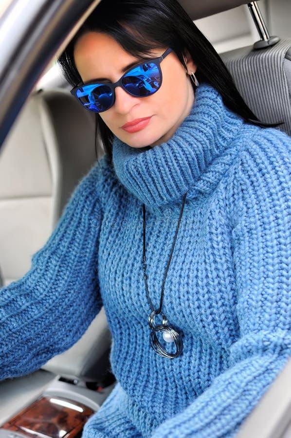 Eine schöne hübsche brunette Frau in einer blauen Strickjacke mit einem Anhänger und Sonnenbrille, die im Auto auf dem Fahrersitz stockbilder
