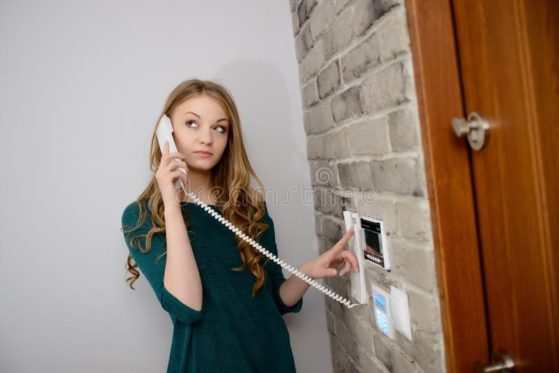 Eine schöne junge blonde Frau, die auf der Wechselsprechanlage spricht stockfoto