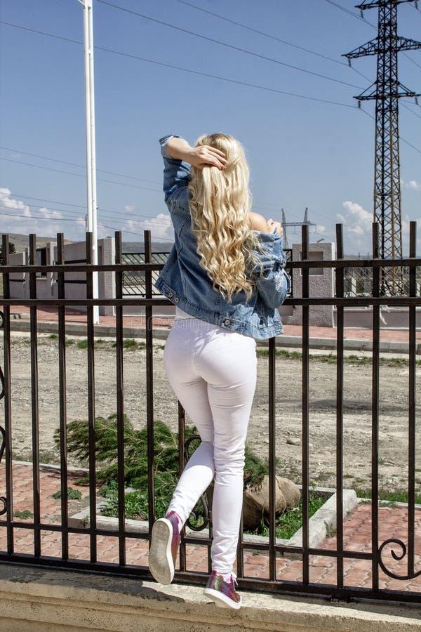 Eine schöne junge blonde Frau steht mit ihrer Rückseite gegen den Zaun stockfotografie