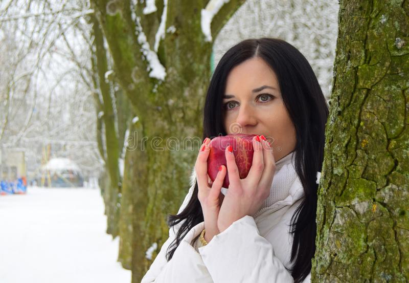 Eine schöne junge Brunettefrau hält einen roten Apfel in ihren Händen stockbild